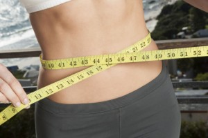 Close-up of woman measuring her waistline